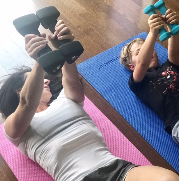 This picture of myself and my son Cole performing a chest press together is one of my favorites.  This is a classic exercise for kids to learn and it will help them whether they are involved in youth sports or with better posture when sitting in the classroom.  This is not in my top safe exercises for kids but one that is important to be taught early on.